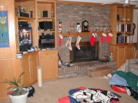 The family room used to be all dark brown barn siding.  It was remodeled fairly quickly.  There are bookshelves all over.  Stockings are hanging, since the pictures were taken soon after Christmas.