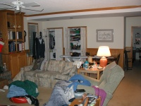 Looking towards the back of the family room, the couch, recliner, and closets can be seen.  The door on the right enters the office.