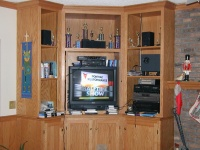 The entertainment center.  Above the TV are assorted trophies, and to the right of the TV is the sound system.
