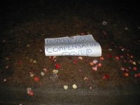 A sign left on the ground by the rose petals.