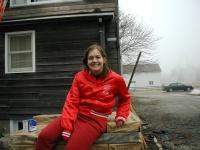 Becki sitting on the pallet of shingles